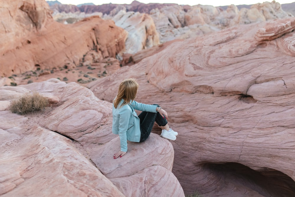 woman in blue jacket sitting on brown rock formation during daytime