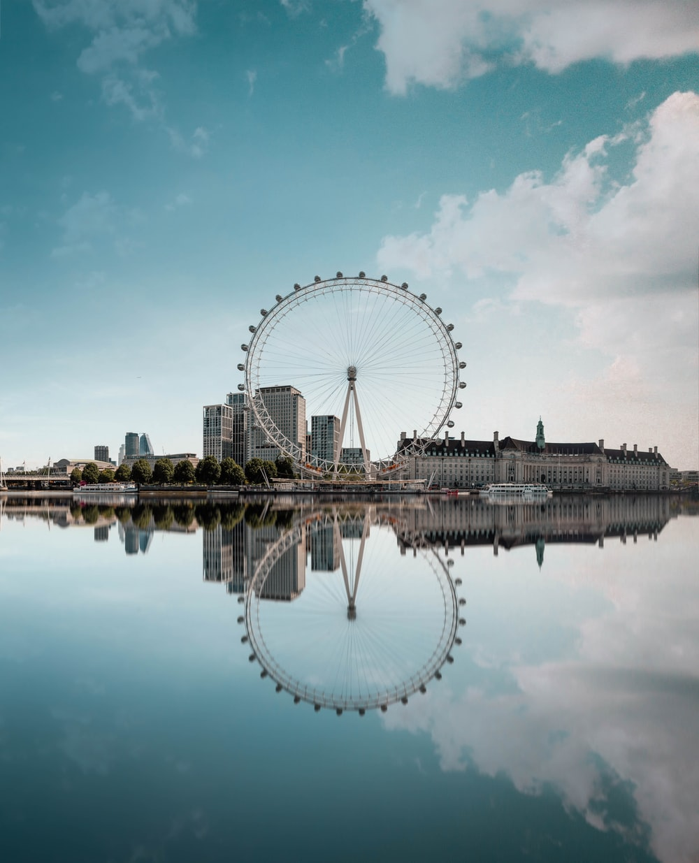 ferris wheel beside body of water under blue sky during daytime