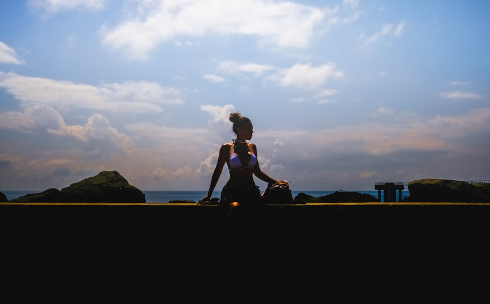 woman in black tank top and black pants sitting on brown wooden fence during sunset