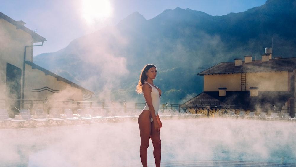 woman in white bikini standing on white sand during daytime