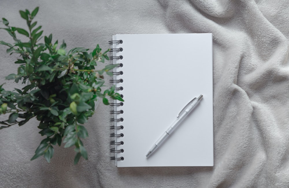 white click pen on white spiral notebook