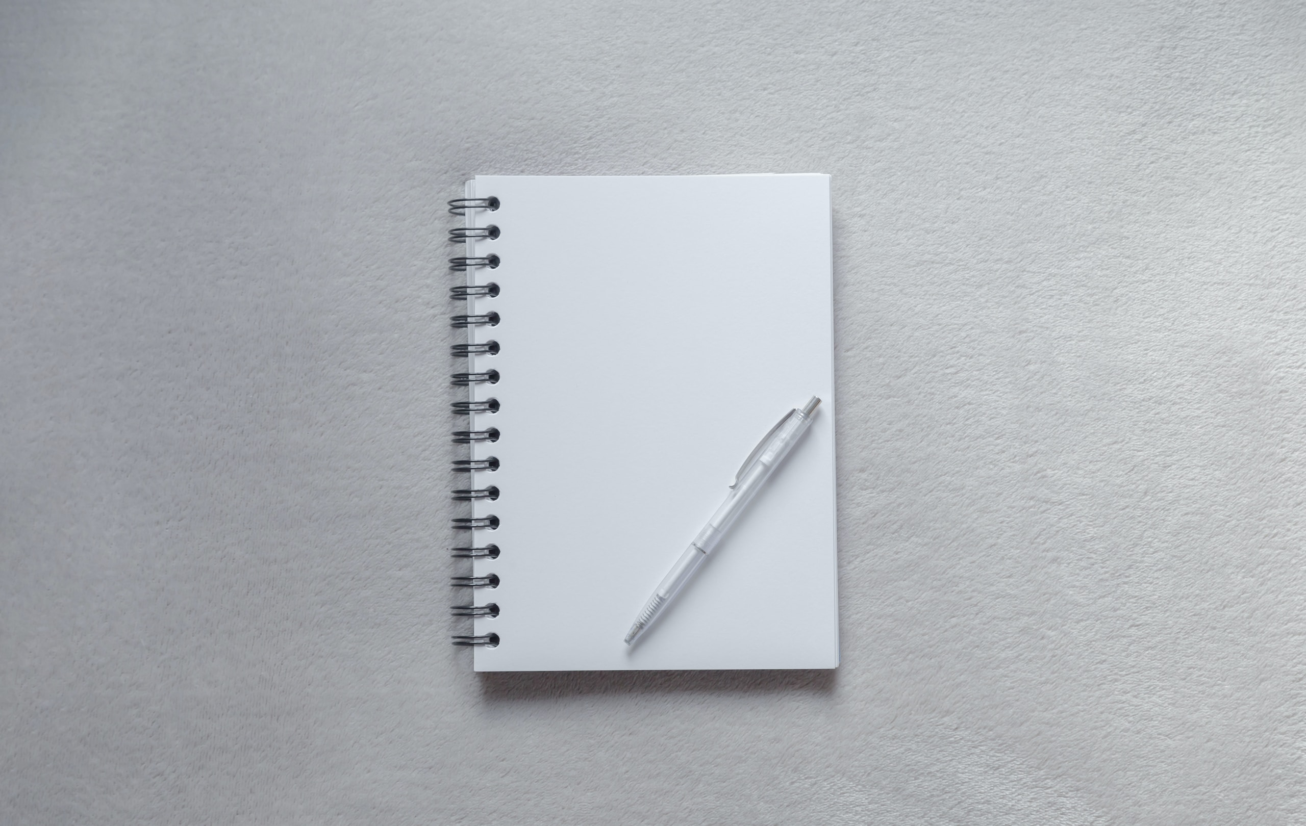 white notebook with pen on top