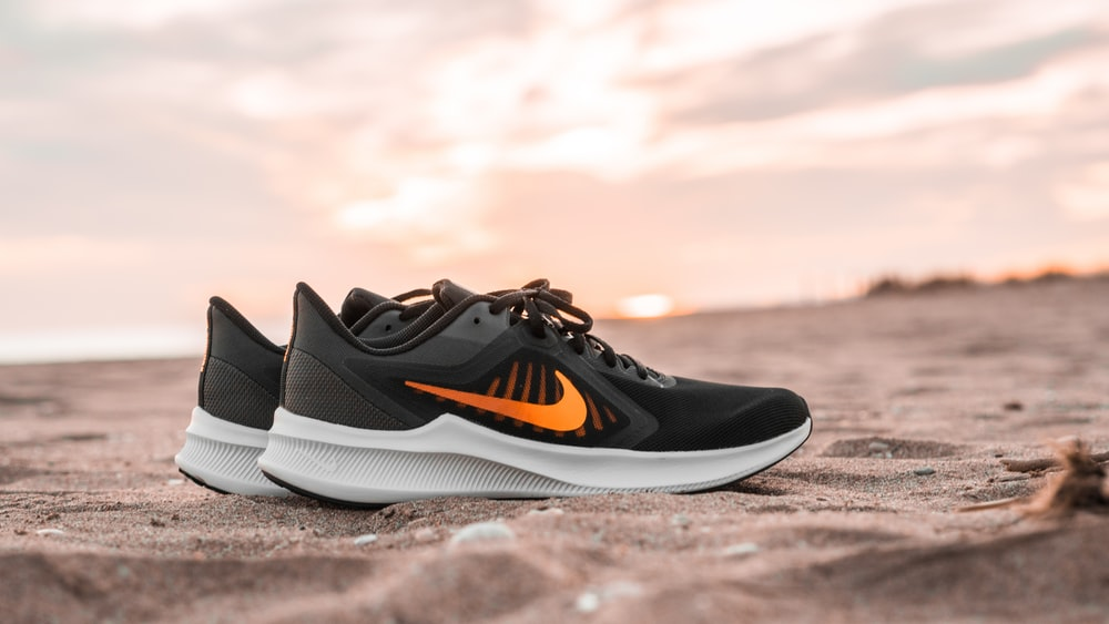 black and white nike athletic shoes on brown sand