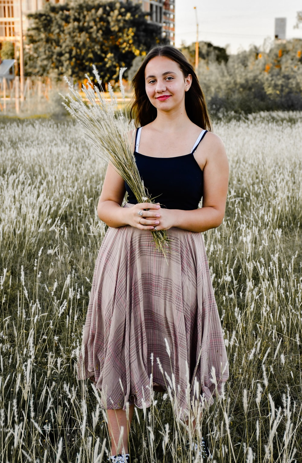 woman in black tank top and gray and white plaid skirt standing on grass field