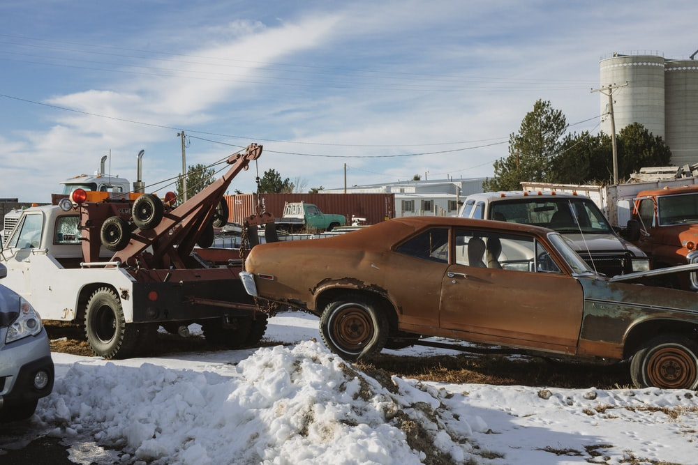 brown and white vintage car on snow covered ground during daytime