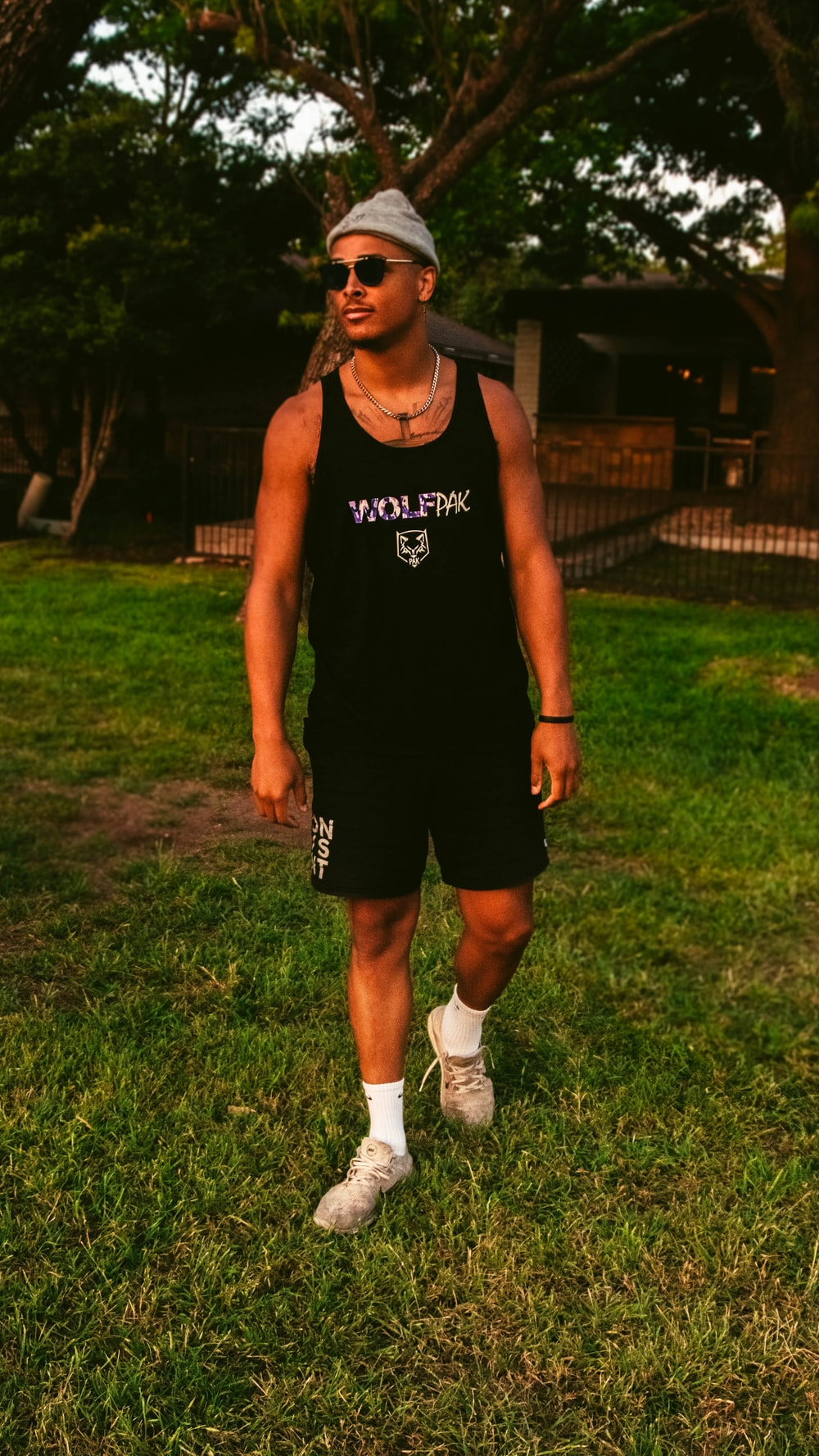 man in black tank top and shorts standing on green grass field