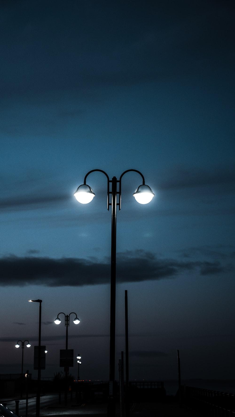 black metal framed light post during night time