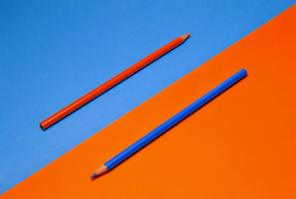 blue pencil on orange surface