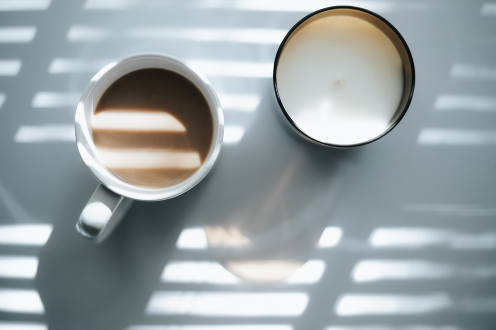 2 white ceramic mugs on white table