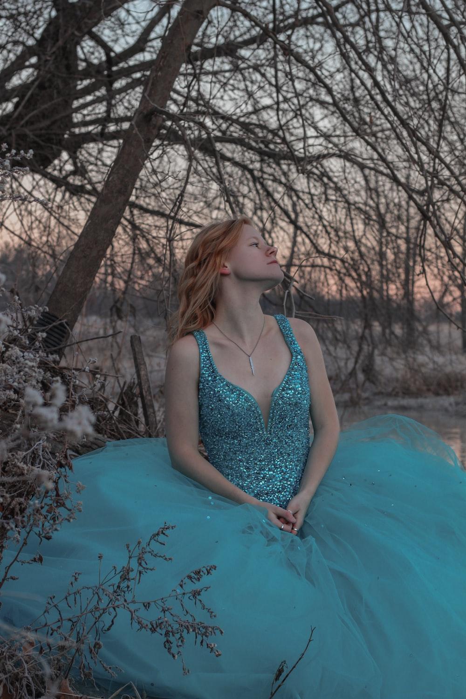 woman in blue spaghetti strap dress sitting on blue water
