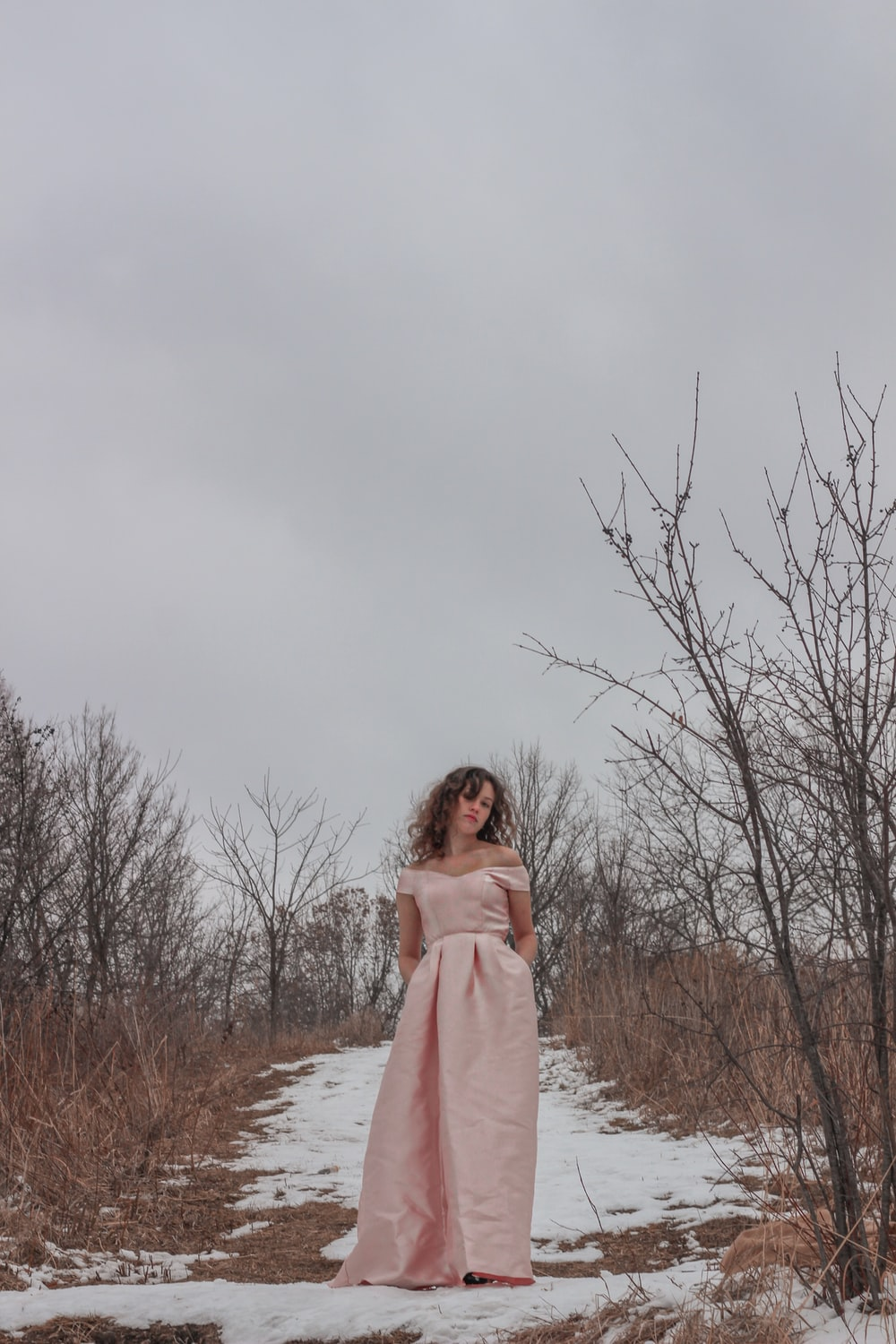 woman in pink long sleeve dress standing on snow covered ground