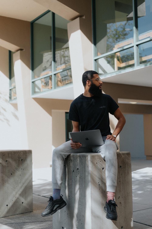 man in black crew neck t-shirt sitting on white concrete bench using macbook