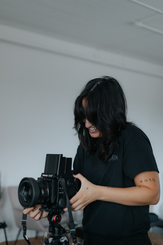 woman in black t-shirt holding black dslr camera