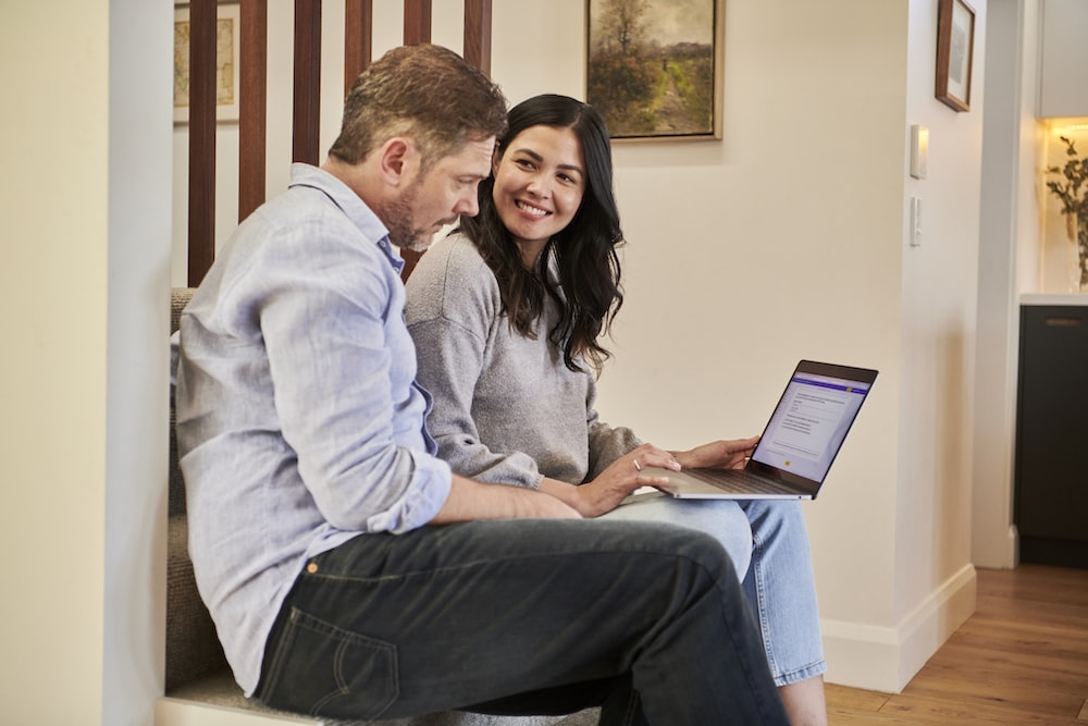 man sitting beside woman looking at a contract on DocuSign