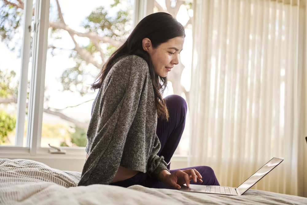 A woman on a bed working on signing a contract with Docusign