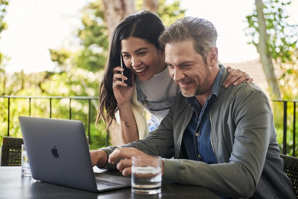 man sitting beside woman looking at laptop