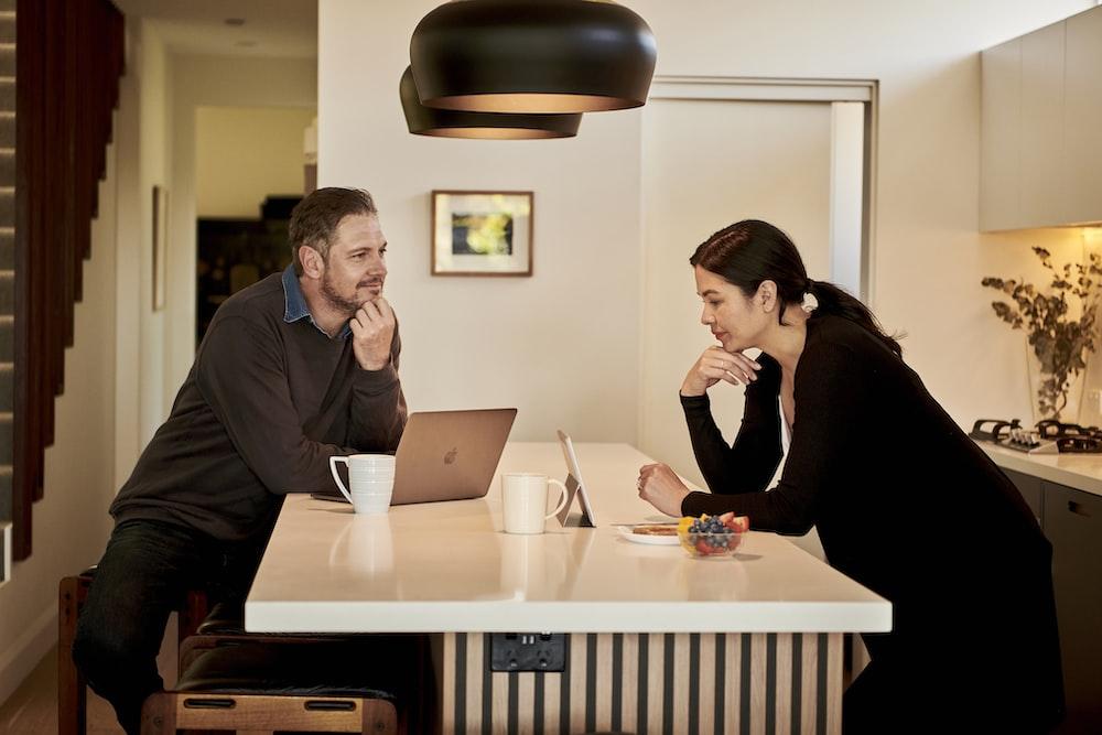 man sitting beside woman in kitchen