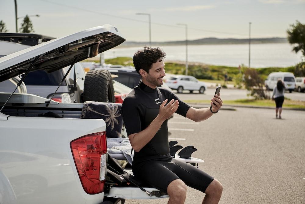 man sitting on car talking on phone