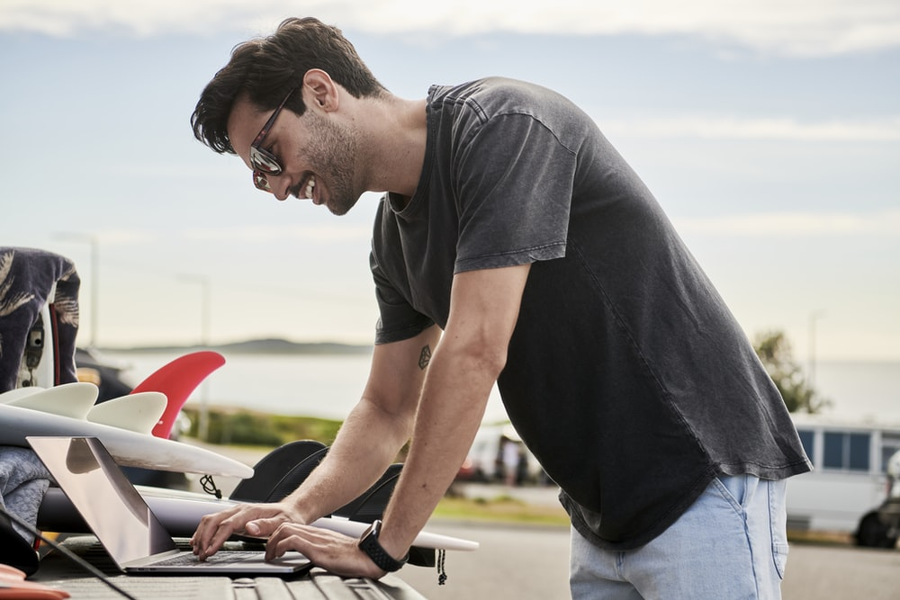 man in gray t-shirt working remotely on a laptop