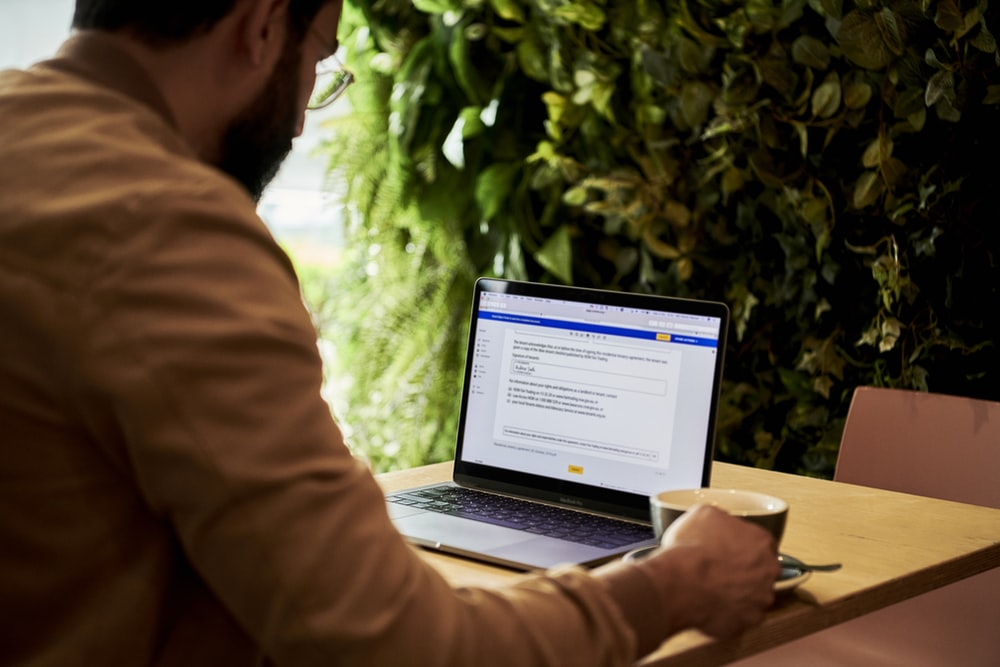 man in brown jacket looking at contract on DocuSign on a laptop