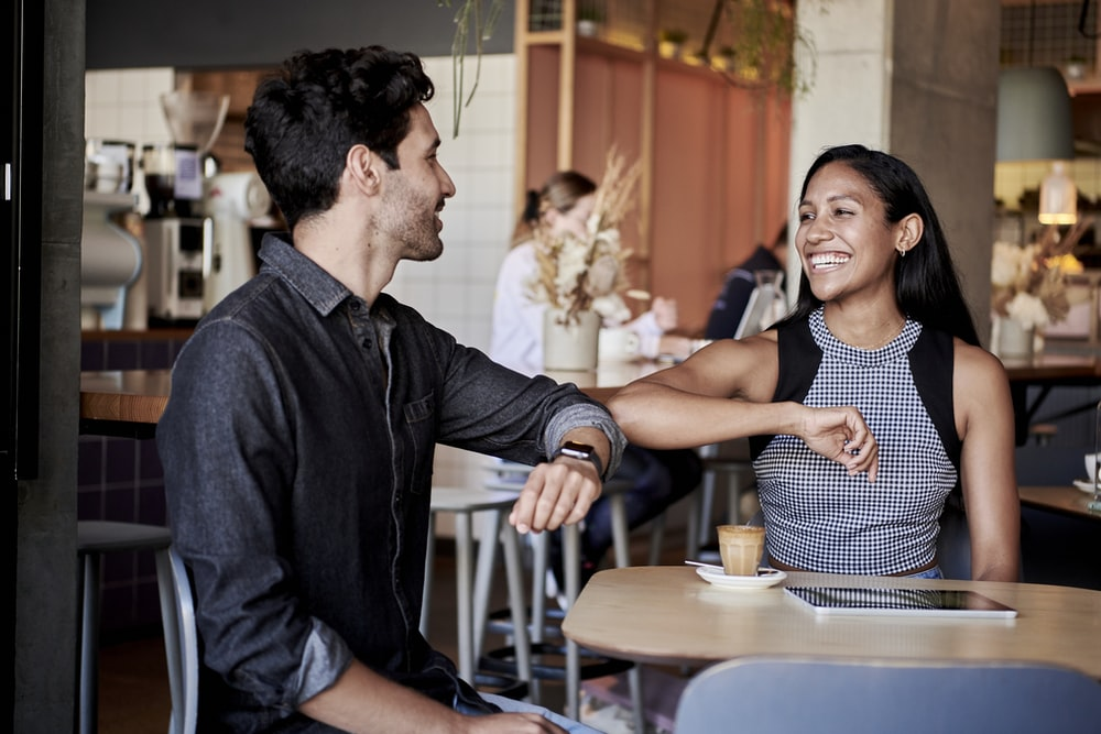 man in black shirt elbow bumping with woman in a restaurant