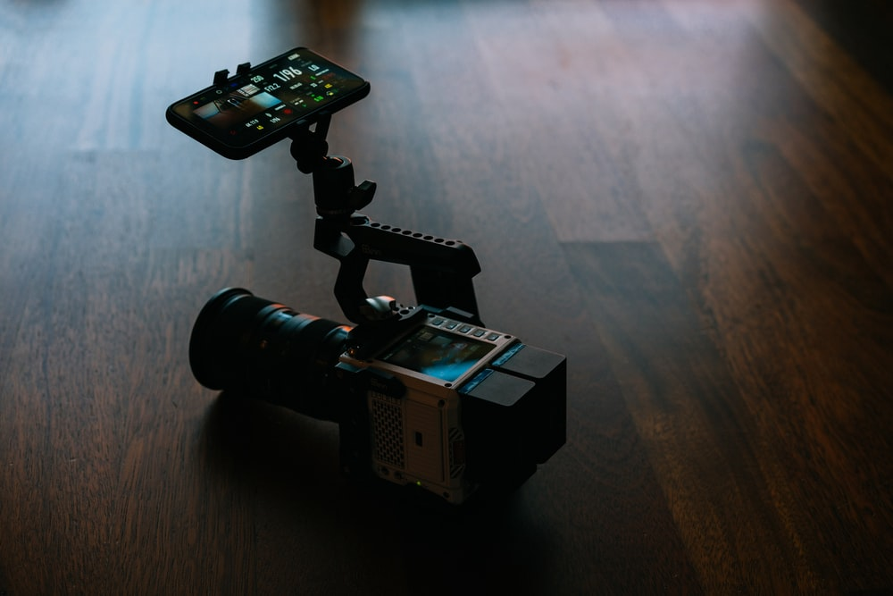 black and gray video camera on brown wooden table