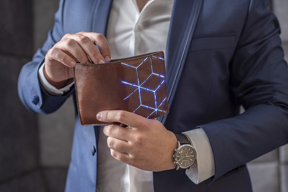man in blue suit jacket holding brown leather wallet