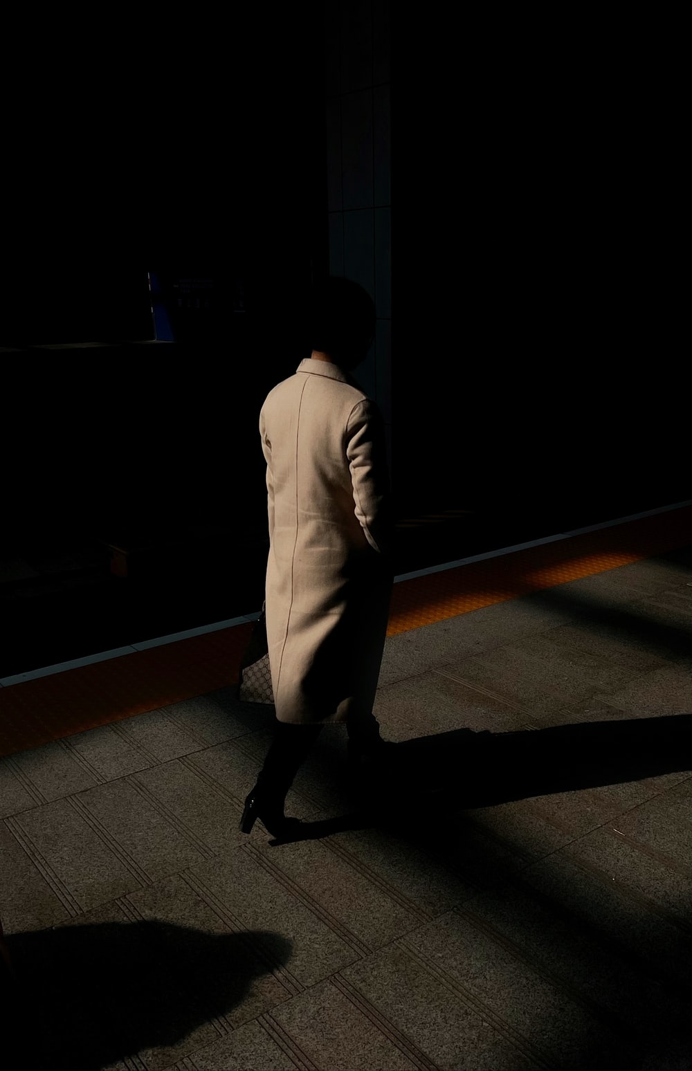 man in white suit walking on brown wooden floor