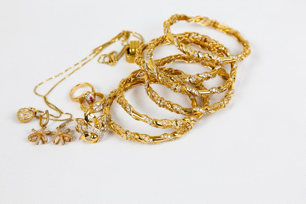 gold chain necklace on white surface