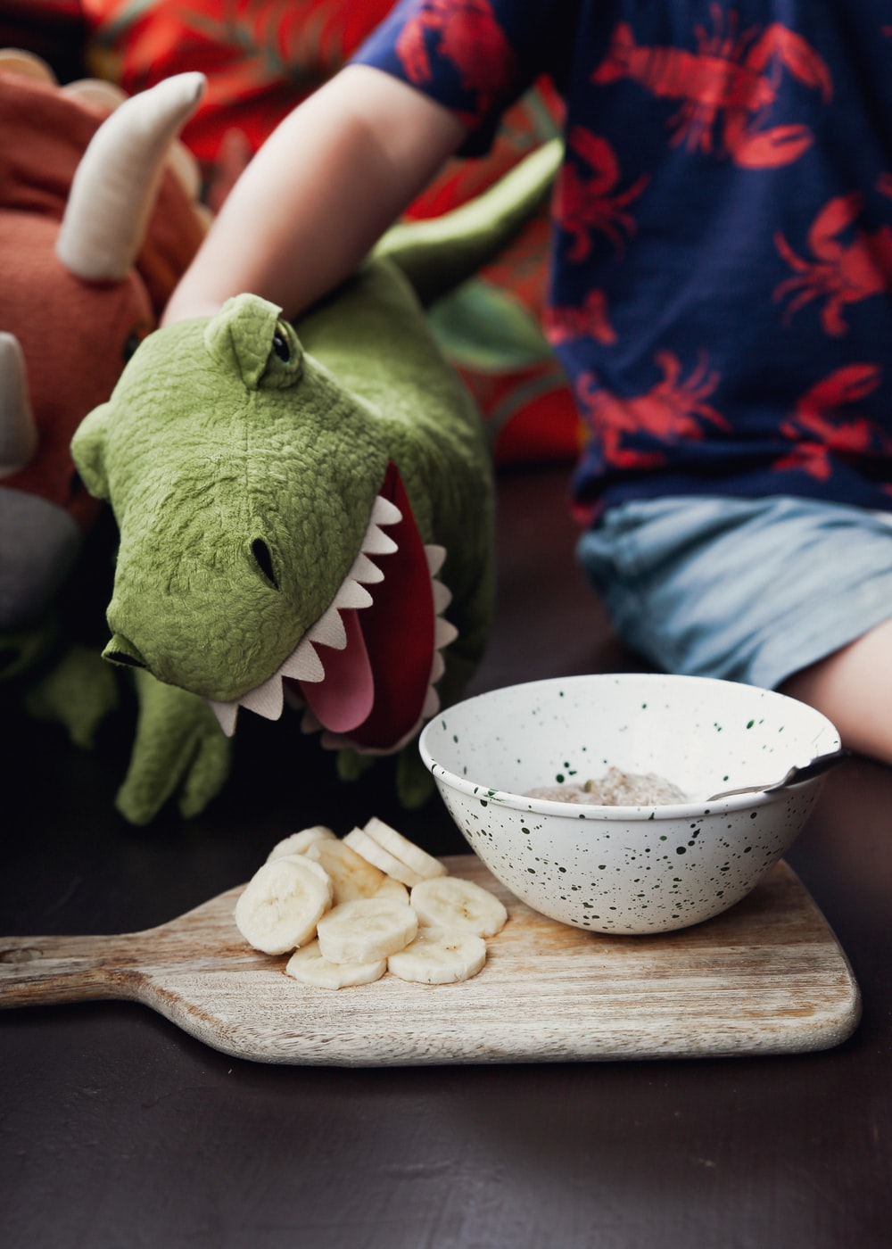green frog plush toy beside white ceramic bowl