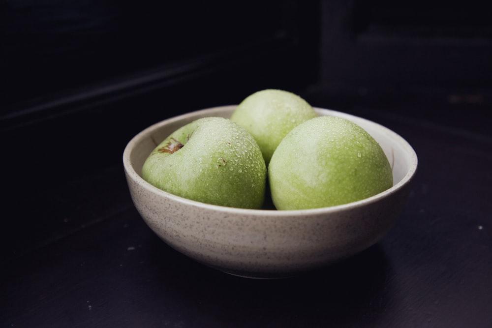 green apple fruit on white ceramic bowl