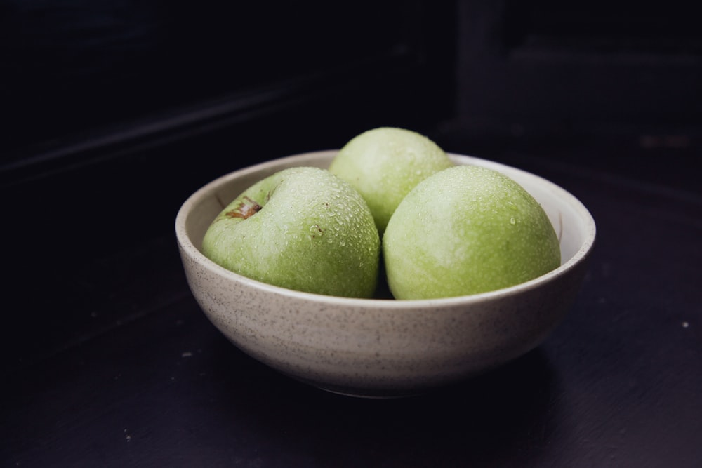 green apple fruit on white ceramic bowl