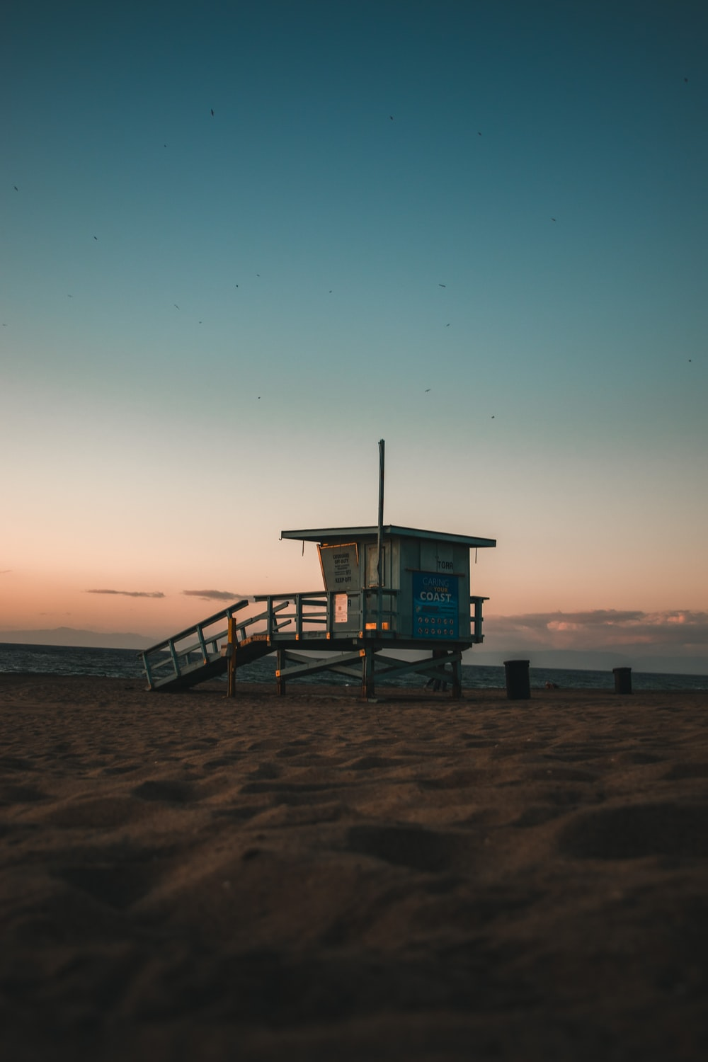 blue lifeguard house on beach during sunset