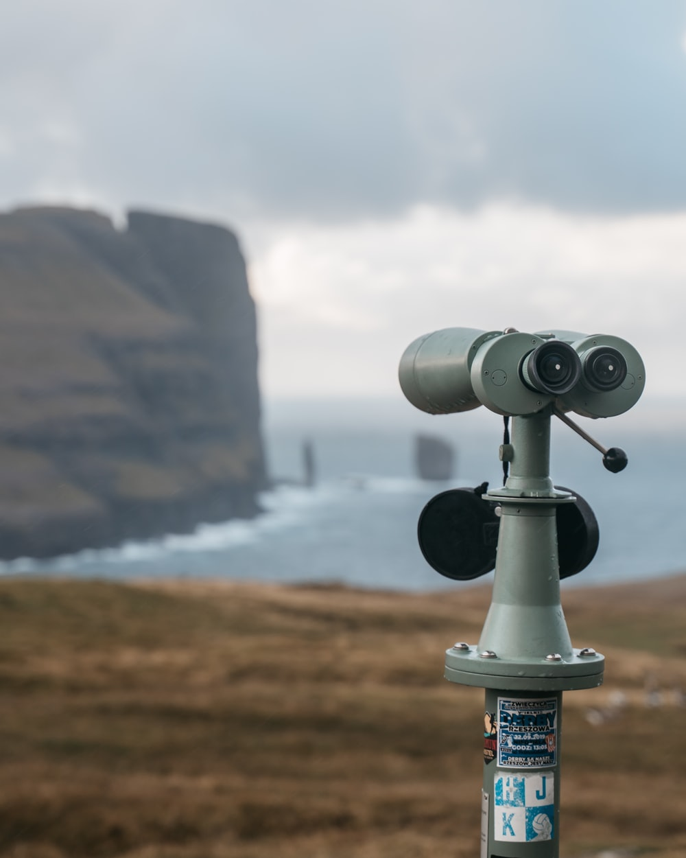 black and gray binoculars on brown rock formation near body of water during daytime