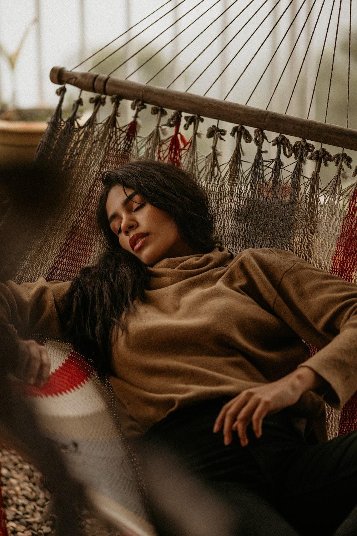 woman in brown sweater lying on floor