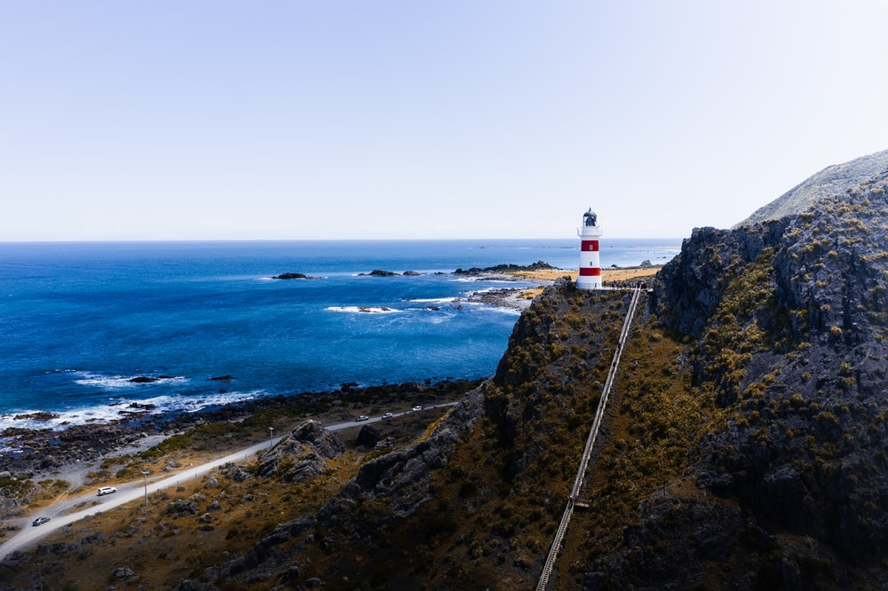 white and red lighthouse on cliff by the sea during daytime