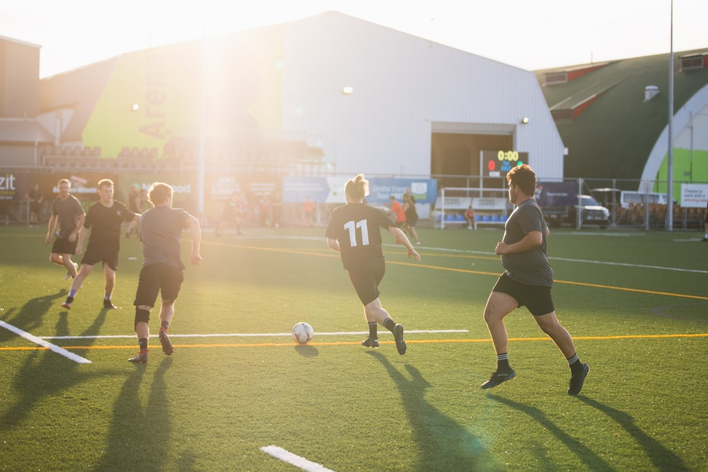 group of men playing soccer on green grass field during daytime