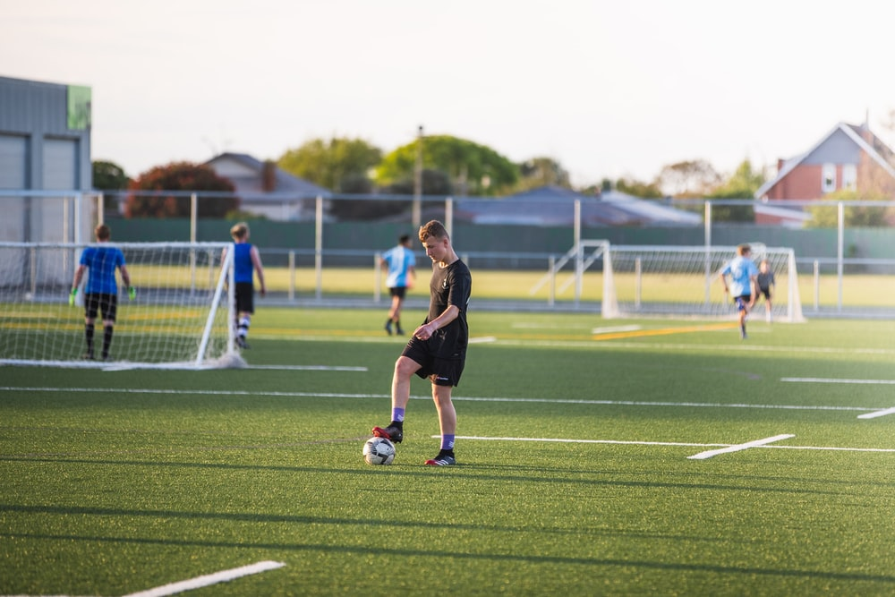 woman in black shirt and shorts playing soccer during daytime
