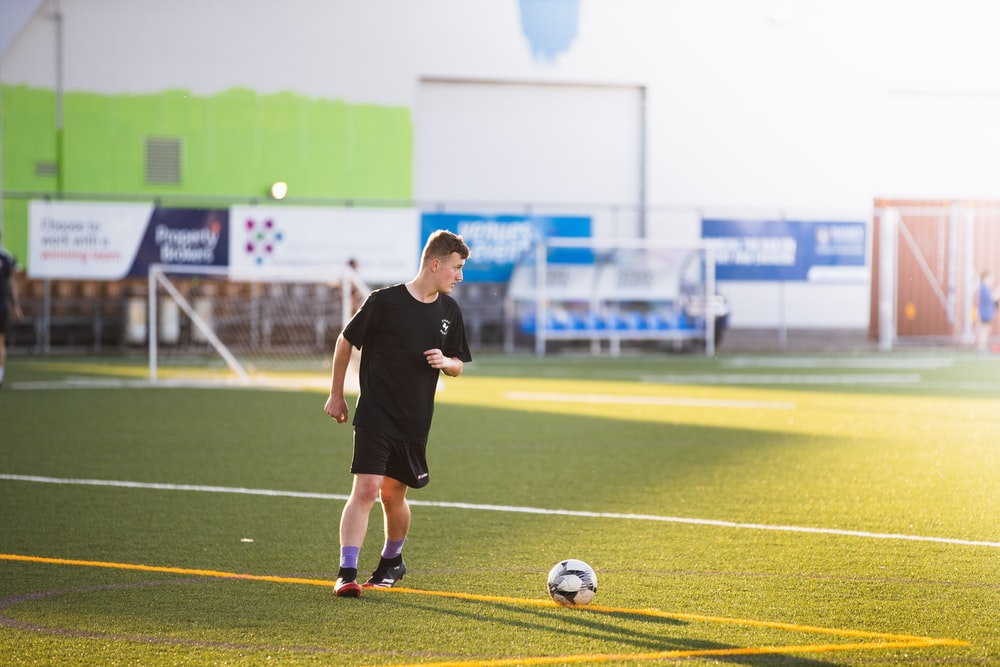 man in black shirt and shorts playing soccer during daytime