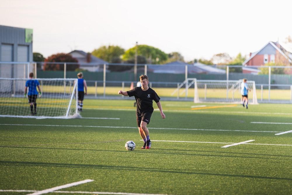 man in black shirt playing soccer during daytime
