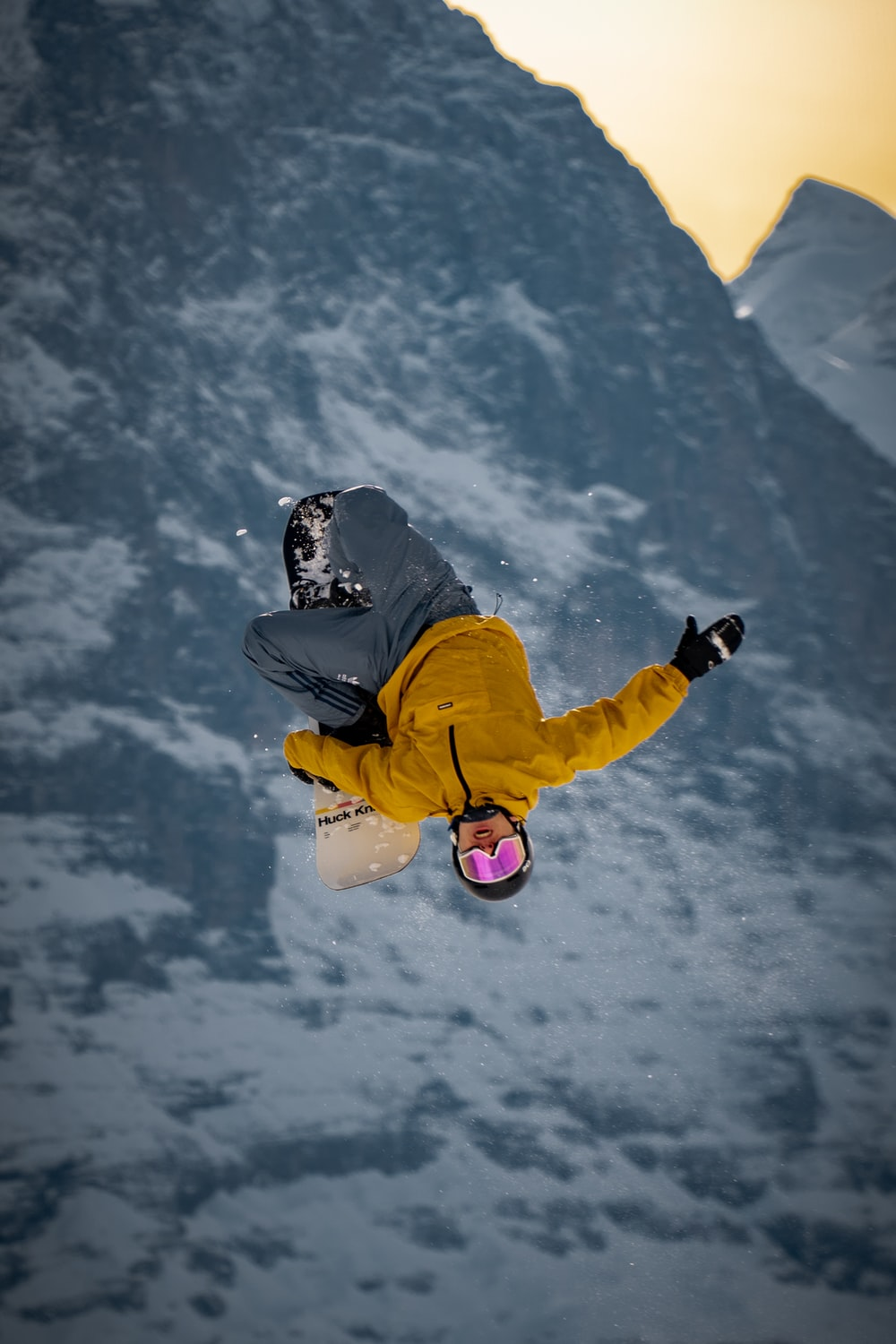 man in blue jacket and yellow pants wearing black helmet jumping on snow covered mountain during