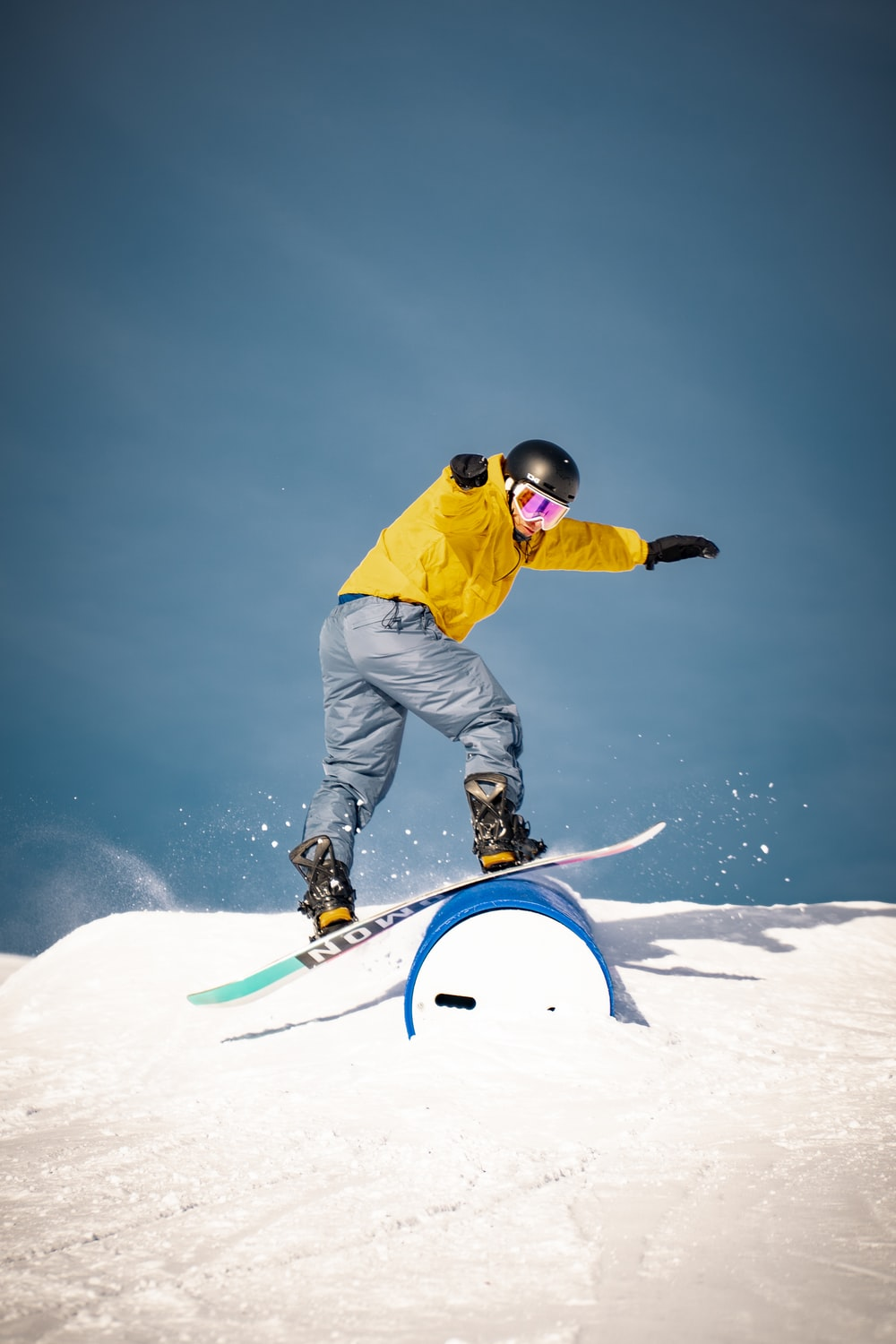 man in yellow jacket and gray pants riding on blue snowboard during daytime