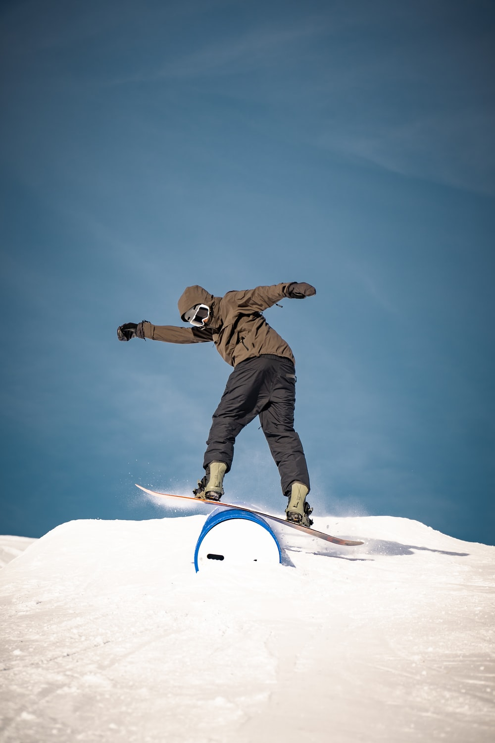 man in brown jacket and black pants riding white snowboard during daytime