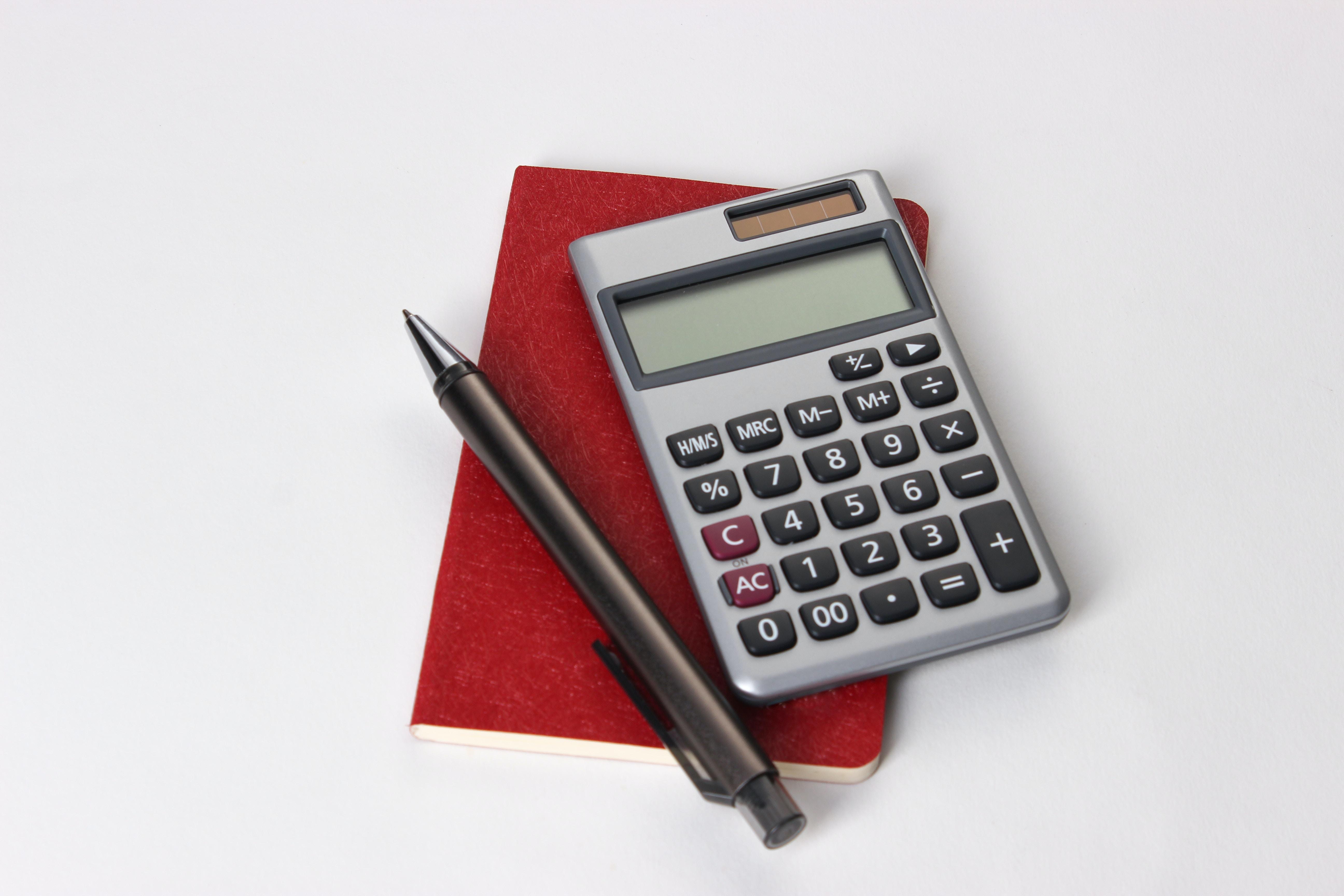 black and silver calculator beside black pen