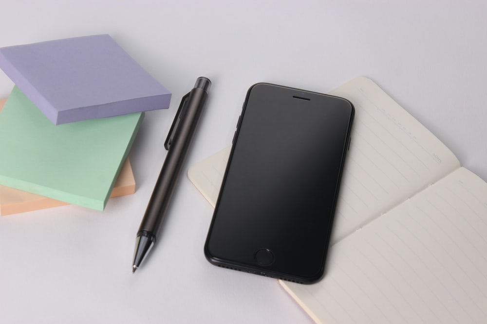 black iphone 4 beside black click pen