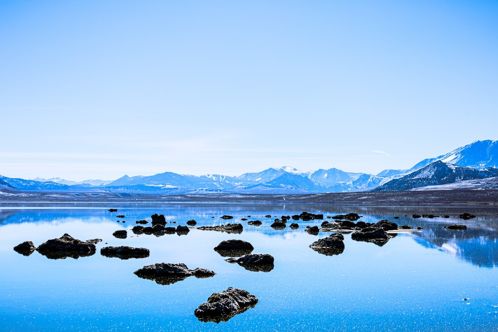 gray rocks on blue body of water during daytime