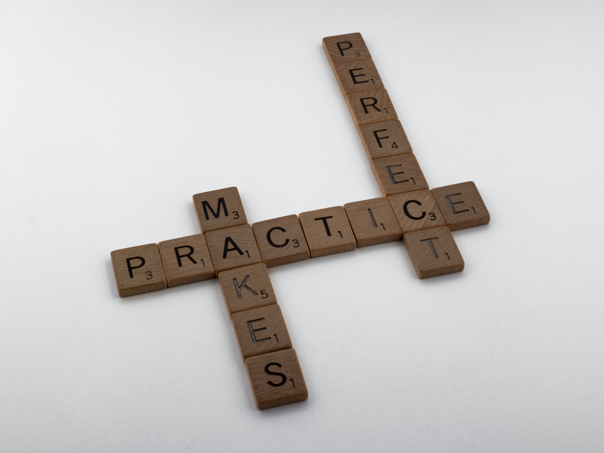 scrabble, scrabble pieces, lettering, letters, wood, scrabble tiles, white background, words, quote, letters, type, typography, design, layout, practice makes perfect, practice, practise, rehearse, try, try again, don't give up, learn, learning, repetition, study,