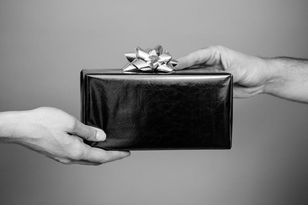 grayscale photo of person holding black leather bifold wallet