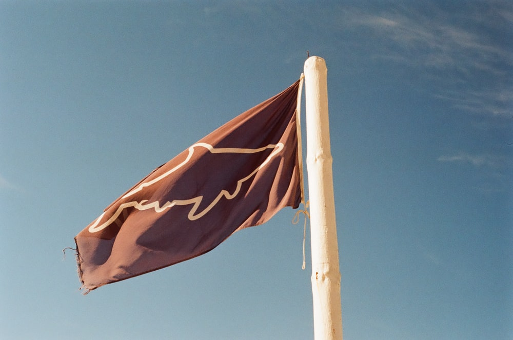 red and yellow flag on pole under blue sky during daytime