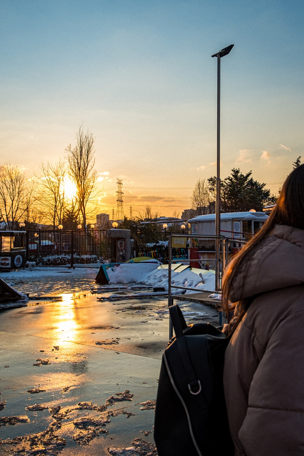 woman in brown jacket standing on snow covered ground during sunset